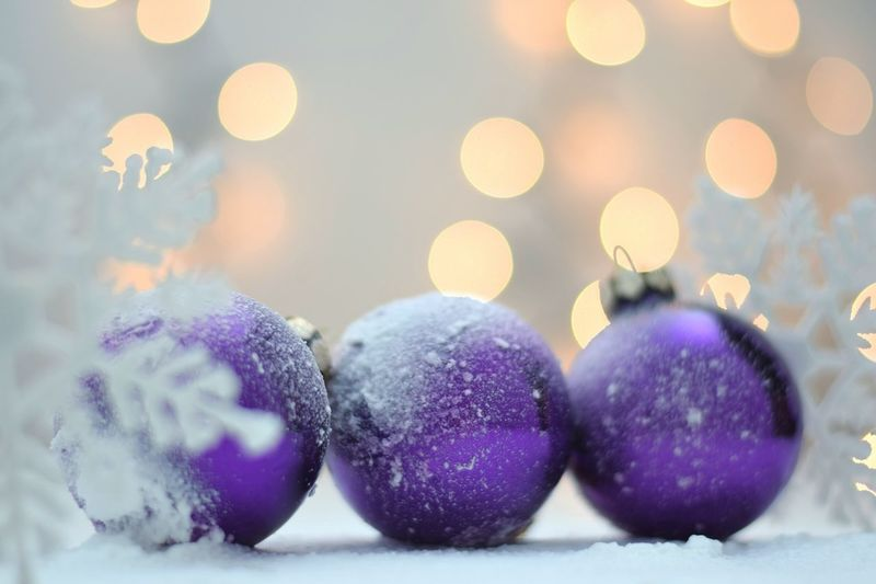 Close-up of purple baubles on snow during christmas