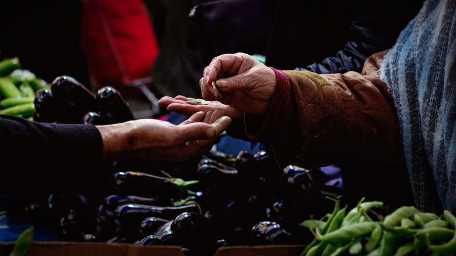 Man giving coin to customer at vegetable stall