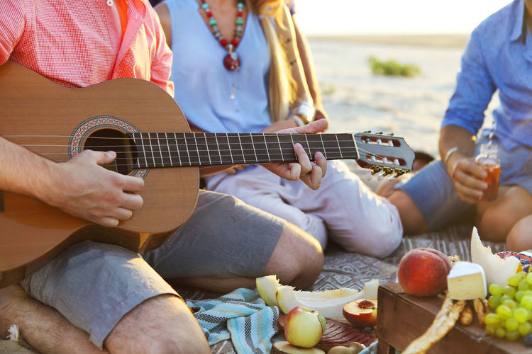 Midsection of man playing guitar while sitting with friends