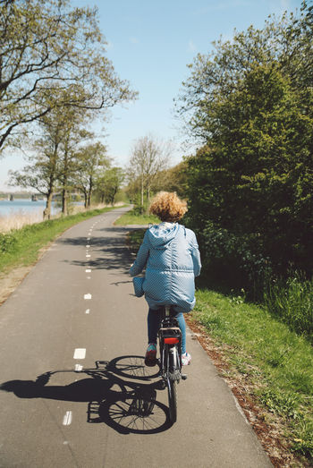 Bicycle Curly Hair Cycling Cycling Helmet Day Full Length Girl Growth Land Vehicle Leisure Activity Lifestyles Mode Of Transport Nature One Person Outdoors Real People Rear View Riding Road Sky The Way Forward Transportation Tree
