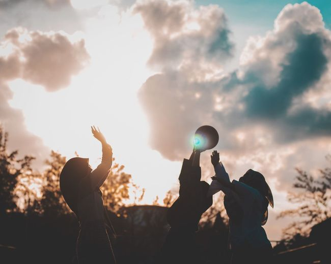 Silhouette friends playing with ball against cloudy sky during sunset