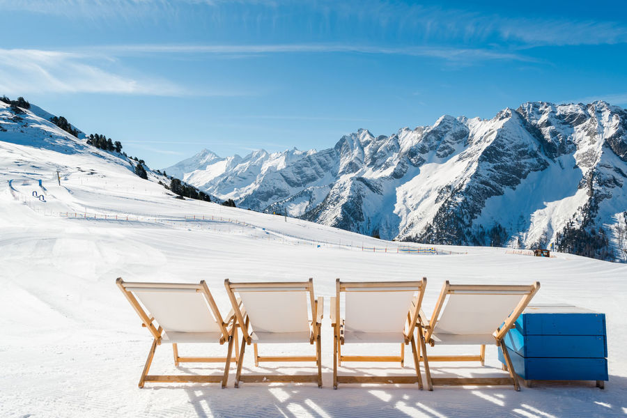Empty white deck chairs on the snow in Mayrhofen ski resort, Austrian Alp Alps Austria Beauty In Nature Clear Sky Cold Temperature Day Deck Chairs Landscape Mayrhofen Mountain Mountain Range Nature No People Outdoors Scenics Sky Snow Snowcapped Mountain Sunlight Tranquil Scene Tranquility Weather White Color Winter