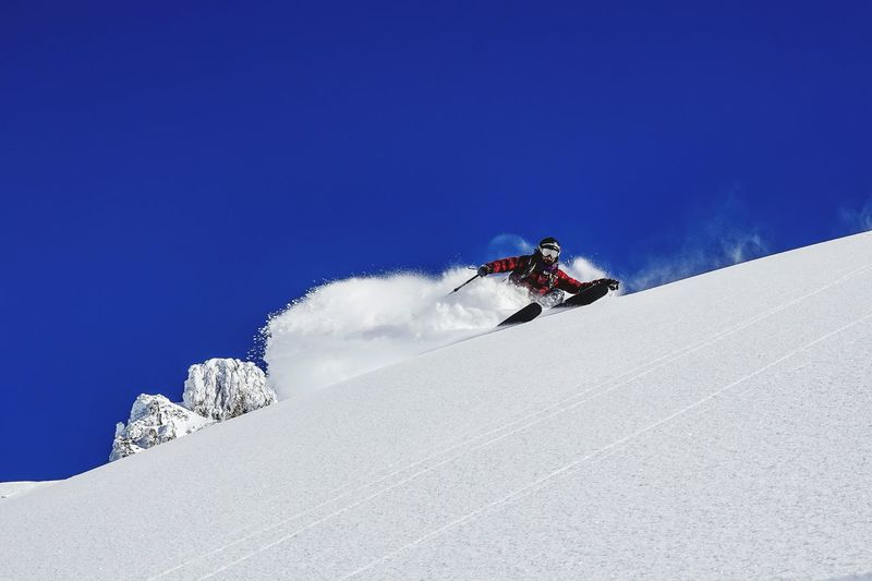 Man skiing on snowcapped mountain against blue sky