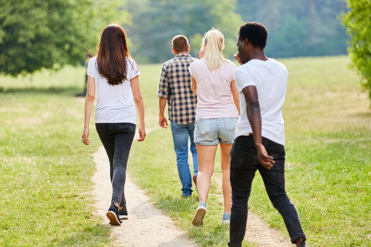 Rear view of friends walking outdoors