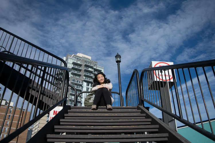 Low angle portrait of smiling young woman sitting on steps against sky