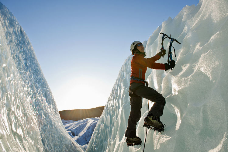 Man climbing on mountain against sky during winter