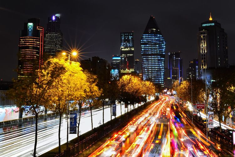 Light trails on street amidst illuminated buildings at night