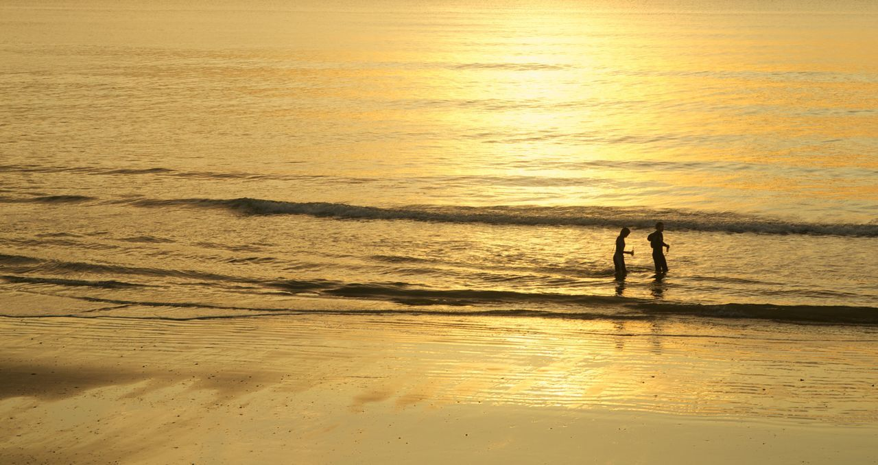 Silhouette Friends Walking At Beach During Sunset