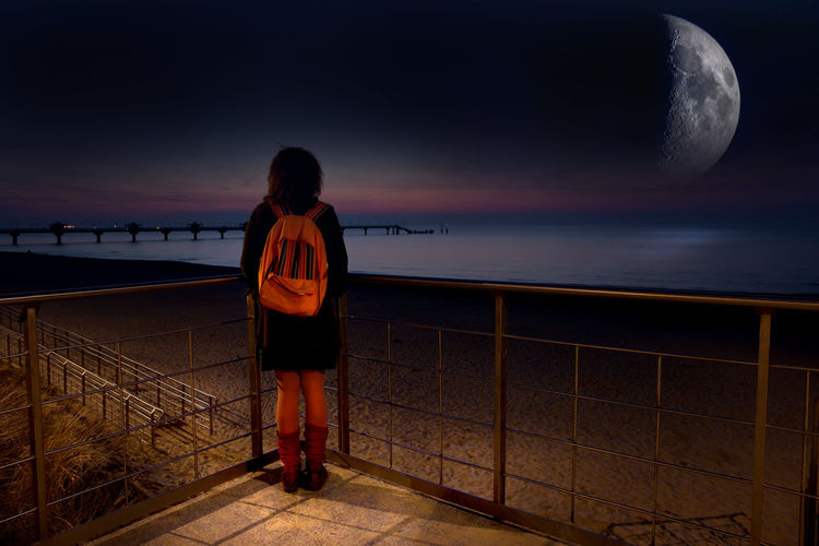 Rear view of woman with backpack looking at sea against sky during night