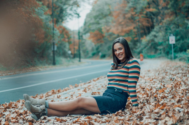 Portrait of smiling young woman sitting on footpath by road