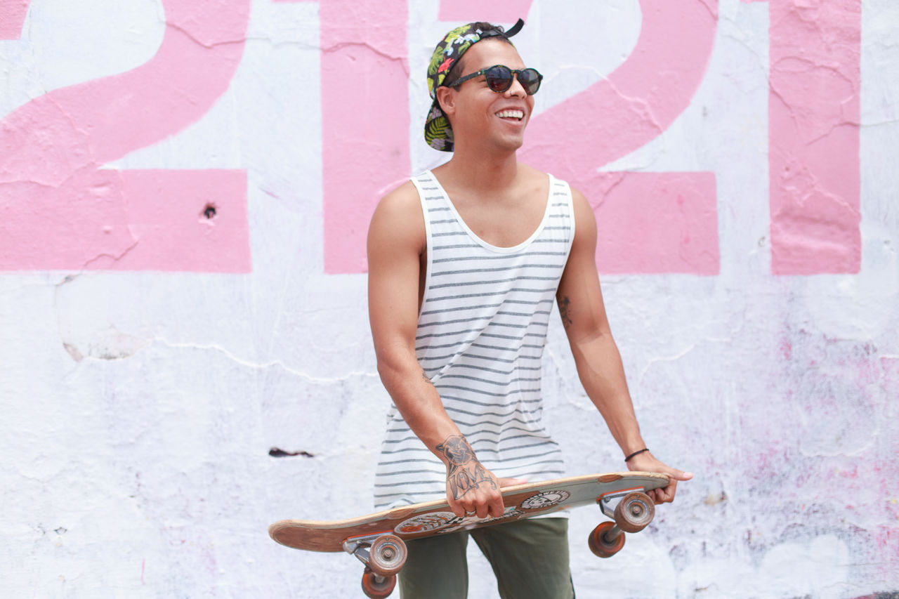 Happy young man carrying skateboard standing against wall