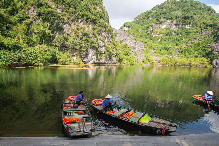 tourist sitting on boat at Trang An, Ninh Binh, Vietnam. Water Transportation Mode Of Transportation Nautical Vessel Day Real People Lake Tree Plant Mountain Nature Group Of People Scenics - Nature Waterfront Beauty In Nature Men Lifestyles Outdoors Inflatable