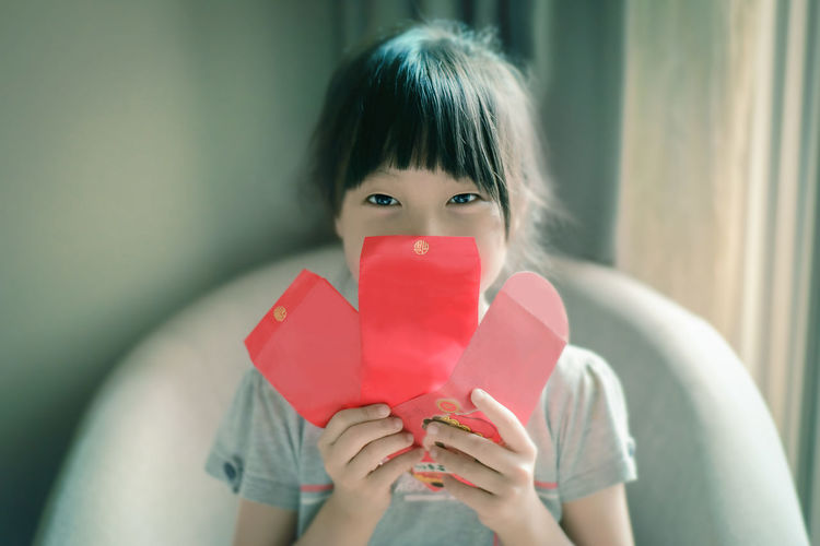 Happy Chinese New Year Asian Girl Casual Clothing Childhood Chinese New Year Day Front View Girls Happiness Holding Indoors  Japanese Ethnicity Lifestyles Lifestyles, Looking At Camera Love Love One Person People Portrait Red Red Envelope Smiling
