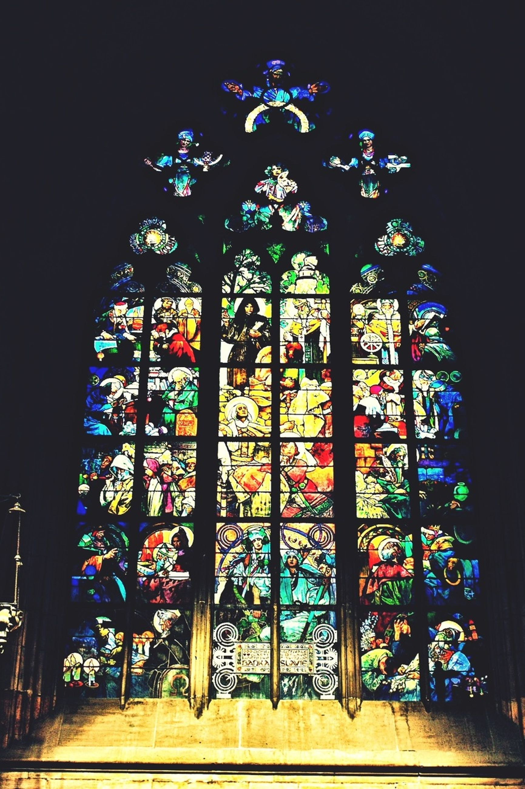 multi colored, place of worship, religion, built structure, architecture, indoors, illuminated, church, stained glass, art, spirituality, art and craft, window, creativity, building exterior, decoration, arch, human representation, night