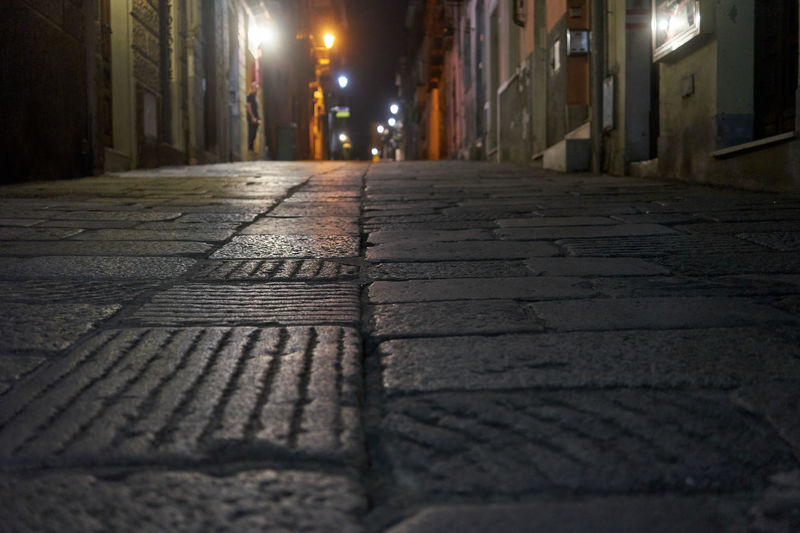 City Street Architecture Illuminated Night Built Structure Building Exterior Direction The Way Forward No People Surface Level Footpath Diminishing Perspective Street Light Outdoors Selective Focus Alley Building Empty Residential District Paving Stone