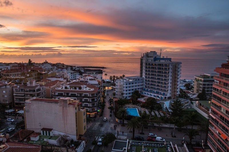 PUERTO DE LA CRUZ, TENERIFE / SPAIN - FEBRUARY 24 2018: View from the Architecture Building Building Exterior Built Structure Car City City Life Cityscape Cloud - Sky High Angle View Mode Of Transportation Nature No People Office Building Exterior Orange Color Outdoors Residential District Romantic Sky Settlement Sky Skyscraper Sunset