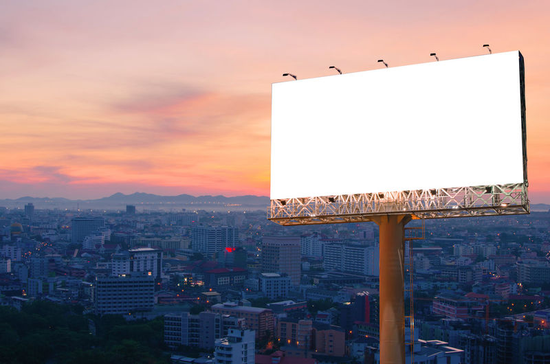 Sunset Architecture Built Structure Building Exterior City Billboard Sky Advertisement No People Nature Copy Space Cityscape Blank Outdoors Orange Color Communication Sign Building Cloud - Sky Illuminated