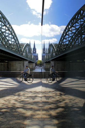 One Person EyeEm Selects Reflection Windows Road Cologne Bike Dom Germany Church Cathedral Place Of Worship Streetphotography Tourism City Cityscape Full Length Bicycle Bridge - Man Made Structure Cycling Suspension Bridge Sky Architecture Railway Bridge Rail Transportation Christianity Railway Track Arch Bridge Catholicism