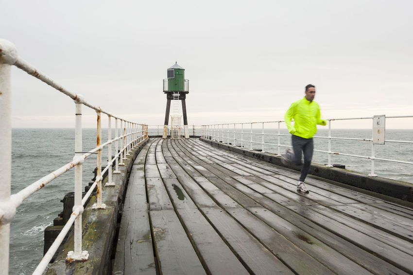 Early morning rain not enough to deter this man from jogging. Taken on a dull morning on Whitby, Yorkshire, UK Adults Only Bridge - Man Made Structure Coast Coastline Day Exercise Jogging Landscape One Man Only One Person Only Men Outdoors Pier Railing Rain Running Sea Seaside Sky Wet Whitby Yorkshire