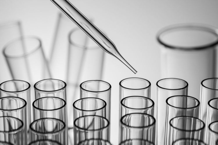 Close-up of pipette and test tube over white background