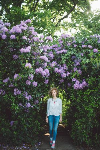 Woman Walking Against Purple Flowering Plants