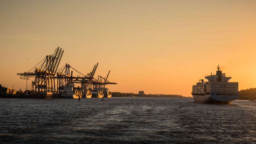 Off to the open sea Globalization Transportation Water Nautical Vessel Sunset Mode Of Transportation Shipping  Freight Transportation Sky Ship Container Ship Transport Cranes Busy