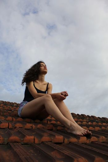 A beautiful woman is sitting on the roof