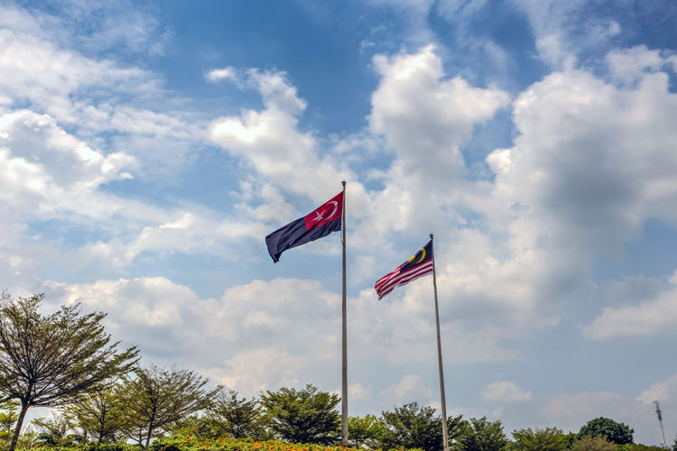 State flag of Malaysia And Johor bahru Flag.Malaysia flag also known as Jalur Gemilang wave with the blue sky. People fly the flag in conjunction with the Independence Day celebration or Merdeka Day.Johor Bahru is One of the states under the administration of malaysia Cloud - Sky Day Environment Flag Independence Low Angle View National Icon Nature No People Outdoors Patriotism Plant Pole Pride Red Sky Symbolism Tree Waving Wind