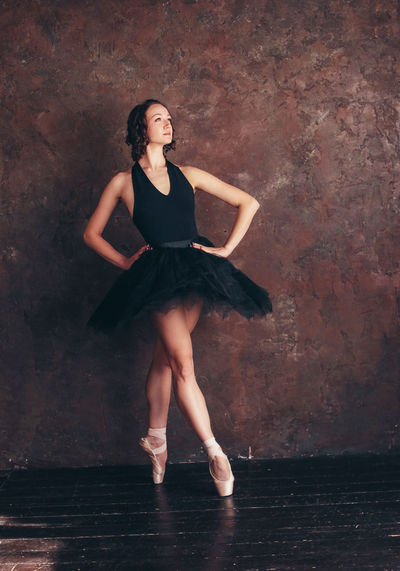 Ballet dancer ballerina in beautiful black dress tutu skirt posing in loft studio Full Length Young Adult Fashion Young Women Women Dress Beautiful Woman One Person Front View Beauty Portrait Real People Adult Clothing Looking At Camera Leisure Activity Wall - Building Feature Indoors  Hairstyle