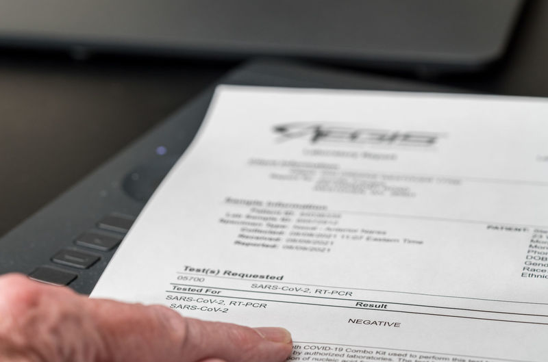Cropped image of person holding paper with text on table