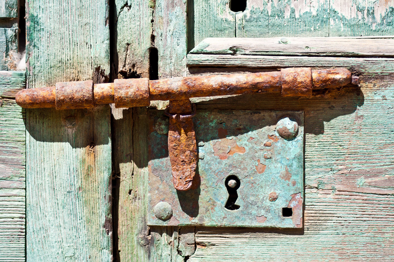 Close-Up Of Rusty Old-Fashioned Latch On Weathered Door