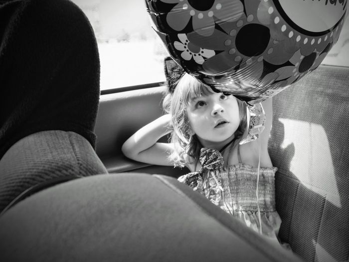 Girl with helium balloon sitting in car