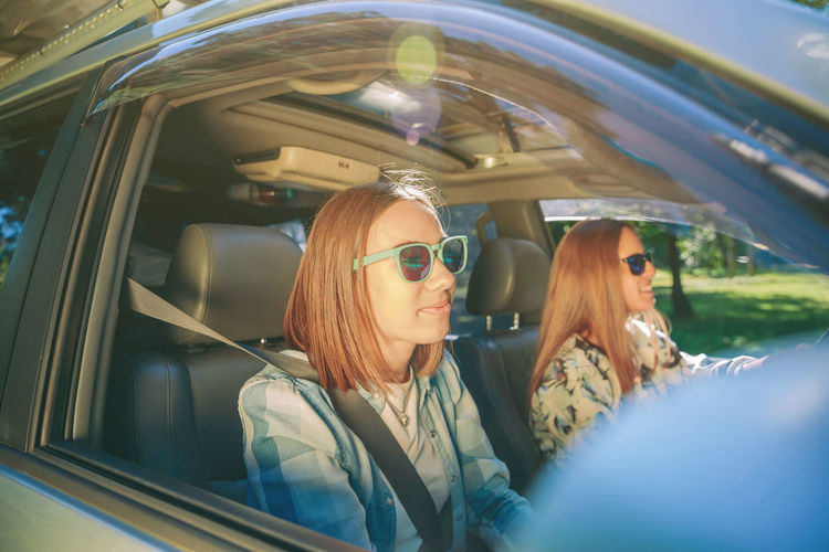 Friends enjoying road trip while traveling in car