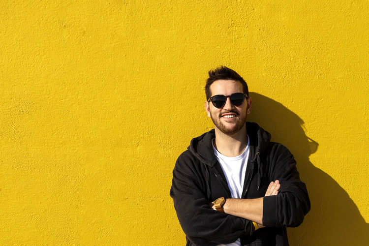 Portrait of young man standing against yellow wall