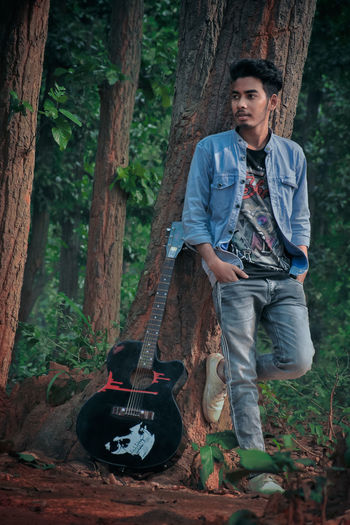 Full length of man standing with guitar by tree in forest