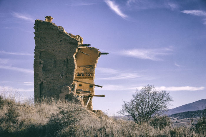 An old ruin in the rural Spanish landscape. Was seen in Aragon, Spain. Aragón Architecture Barn Blue Building Exterior Built Structure Cloud - Sky Daroca Day Grass Low Angle View Nature No People Outdoors Ruin Ruined Ruined Building Ruins Rural Sky SPAIN Tranquil Scene Tranquility Tree Village