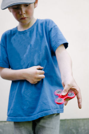 Boy playing with fidget spinner gadget Attention Boy Childhood Close-up Concentration Day Defilé Fidget Spinner Focus Focus On Foreground Gadget Human Hand Kids Leisure Activity Meditative One Person Outdoors Real People Syndrome Tool Toy