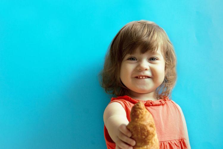Portrait of smiling girl against blue background