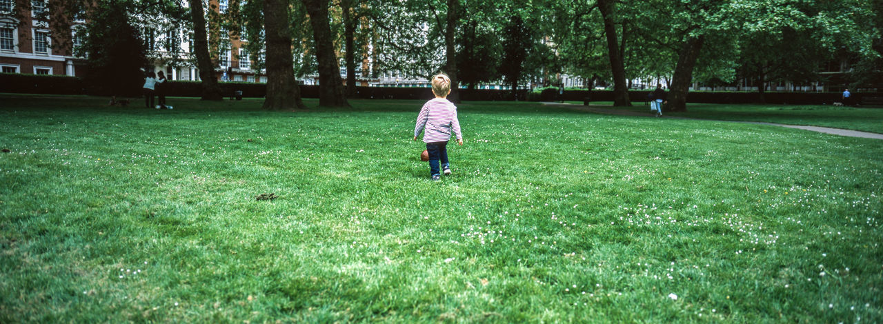 Kid playing football in a park in London Plant Grass Tree One Person Green Color Real People Nature Land Casual Clothing Growth Full Length Lifestyles Field Day Leisure Activity Rear View Walking Outdoors Childhood Xpan London Park Football