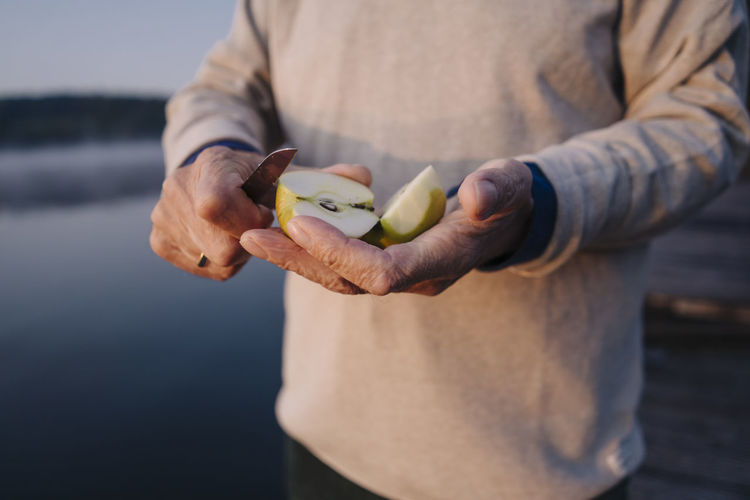 Midsection of man holding fruit while standing outdoors