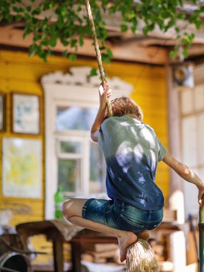 Rear view of boy swinging on rope