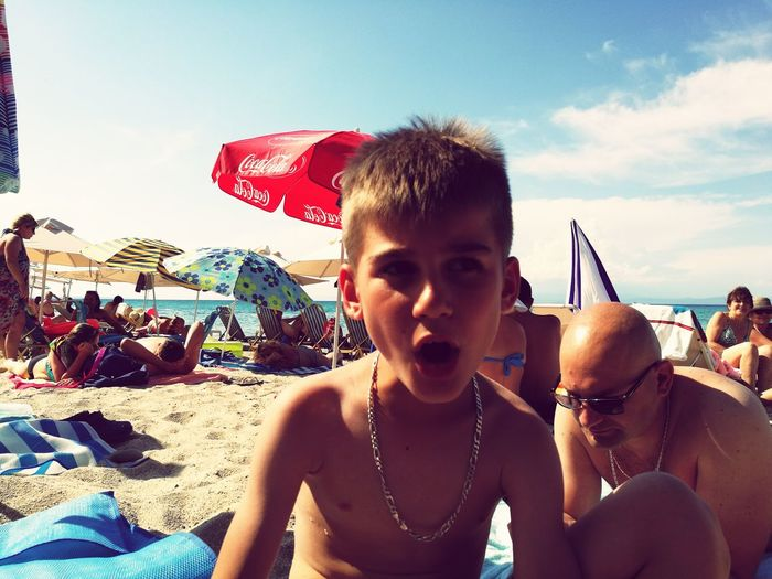 Shirtless boy with mouth open looking away while sitting at beach during summer