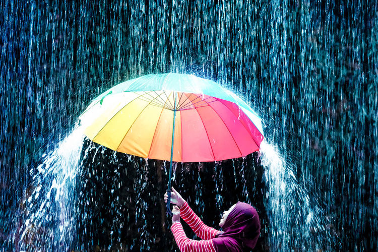 Teenage girl holding colorful umbrella while standing in rain