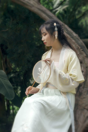 Woman wearing traditional clothing while holding hand fan in forest
