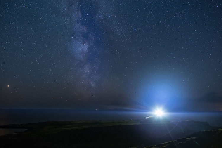 Scenic view of sea against star field at night