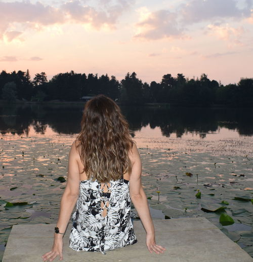 Rear view of woman sitting on pier over lake against sky during sunset