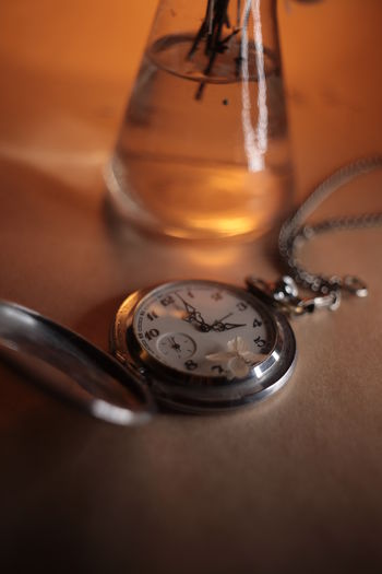 High angle view of pocket watch on table