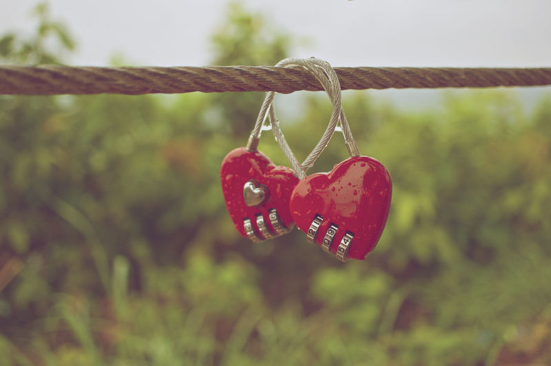 Couple of red padlock with water drop at wire rope in vintage style. Couple Rain Red Retro Rope Drop Hanging Heart Heart Shape Key Lock Love Number Padlock Password Protection Red Safe Safety Security Style Valentine's Day - Holiday Vintage Water Wire