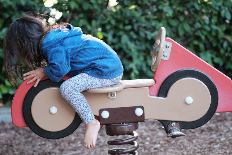Side View Of Girl Sitting On Spring Ride At Park