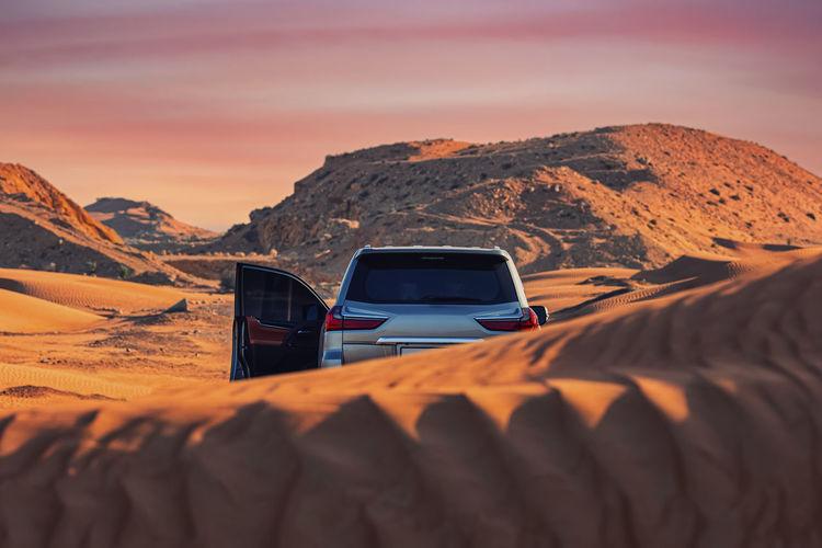 Car on desert against sky during sunset